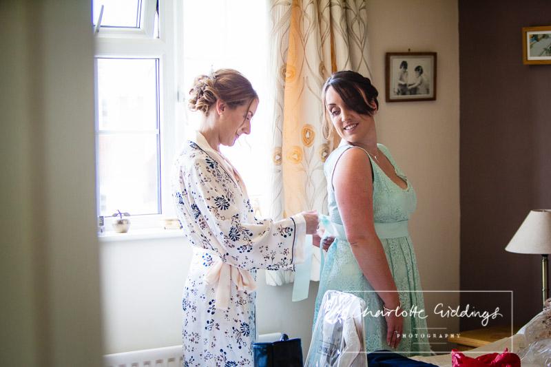 bride helping bridesmaid into her dress
