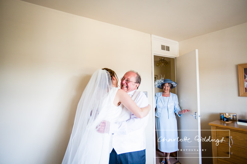 excited father of the bride seeing his daughter in her wedding dress