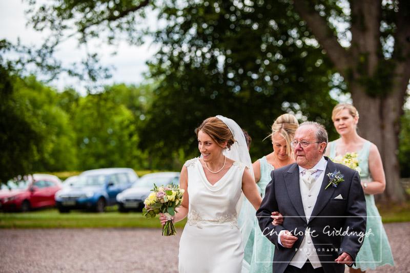 bride walking to ceremony at soulton hall