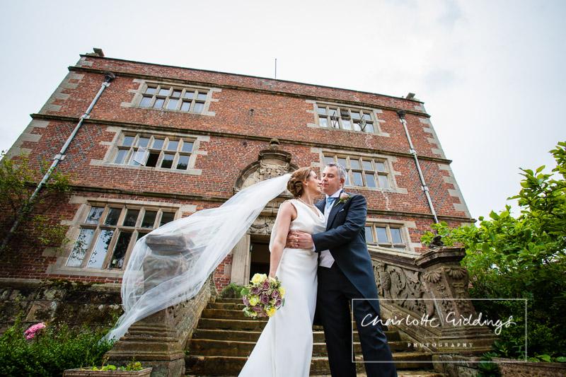 bride and groom veil shot outside soulton hall