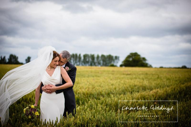 veil shot in wheat field bride and groom