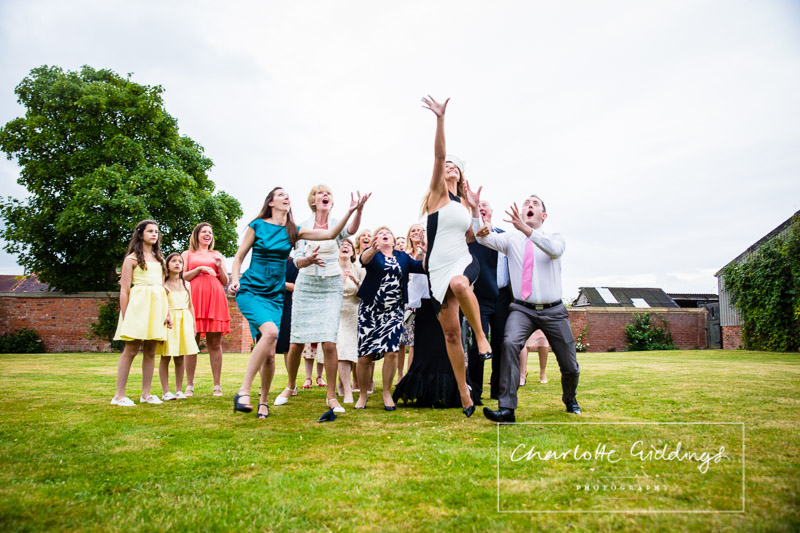 action shot reaching for the brides bouquet