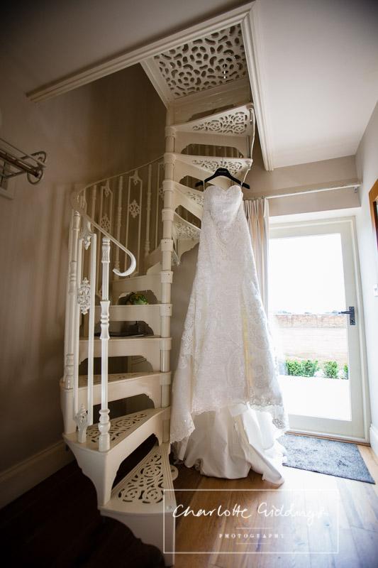 full length shot of lace wedding dress hanging in willington lodge, shropshire wedding