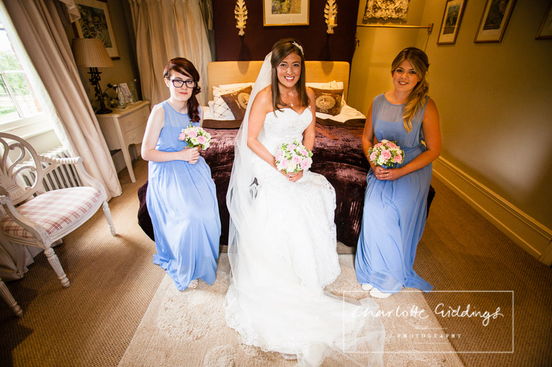 bride and bridesmaids with flowers and fully dressed i natural light at end of bed willington lodge