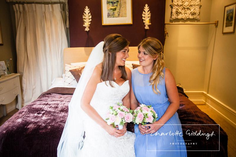 portrait of bride looking at sister bridesmaid in cornflour blue dress shropshire wedding photographer