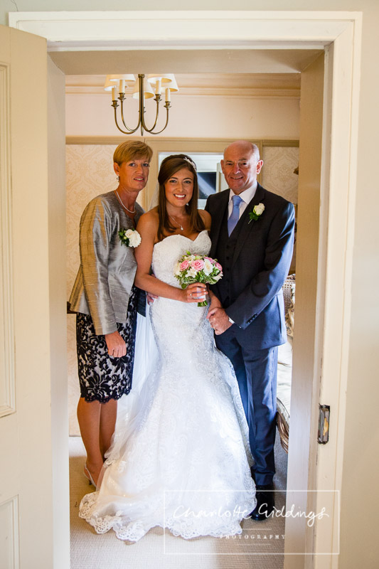 bride, father of the bride and step mother of the bride portrait framed with the door way before they go to church
