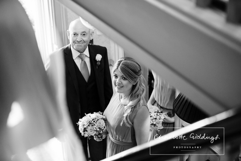 black and white photo of brides sister and dad watching the bride coming down the stairs - summer wedding combermere abbey