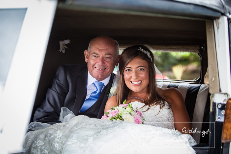very happy father and daughter sat in wedding car ready to go to church