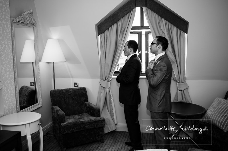 groom and best man both doing up their ties looking in the mirror shropshire wedding photographer