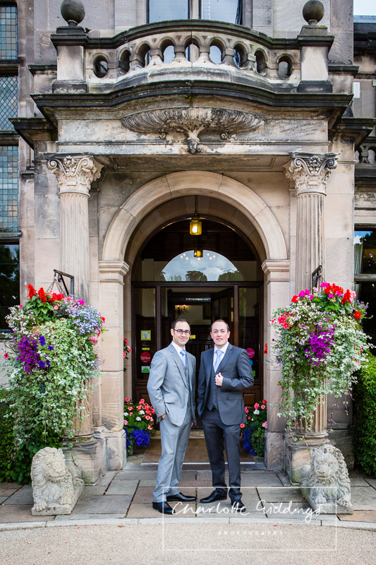 full length shpt of groom and best man looking happy outside of rookery hall hotel entrance
