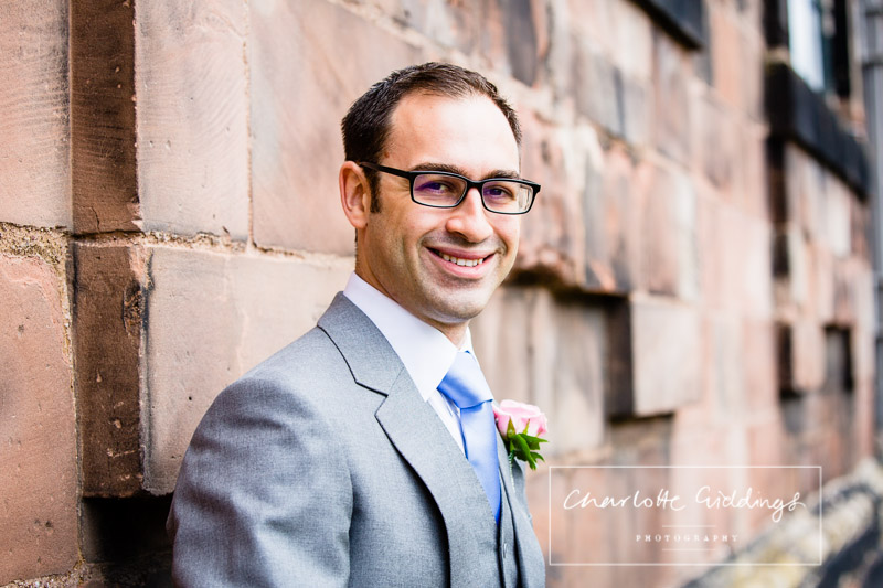 portrait of the groom looking happy before the ceremony along sandstone wall of st.alkmunds church