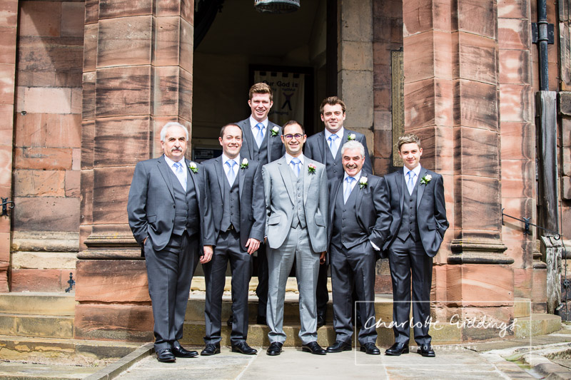 groom, best man and ushers standing relaxed outside the front of st. alkmunds church whitchurch, wearing grey suits