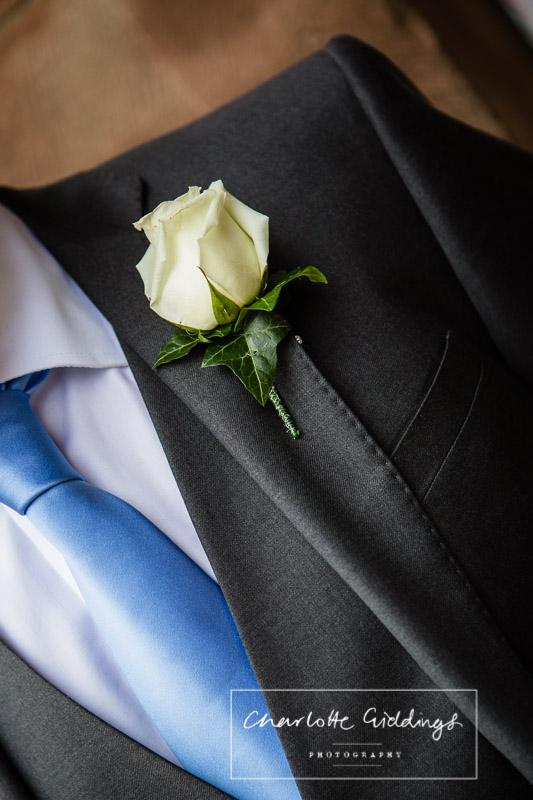 detail of cornflour blue tie, grey suit and cream rose button hole - shropshire wedding photographer
