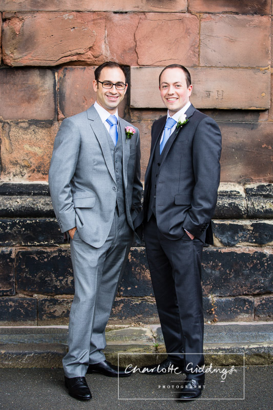 best man and groomo portrait against sandstone wall of st. alkmunds church whitchurch shropshire