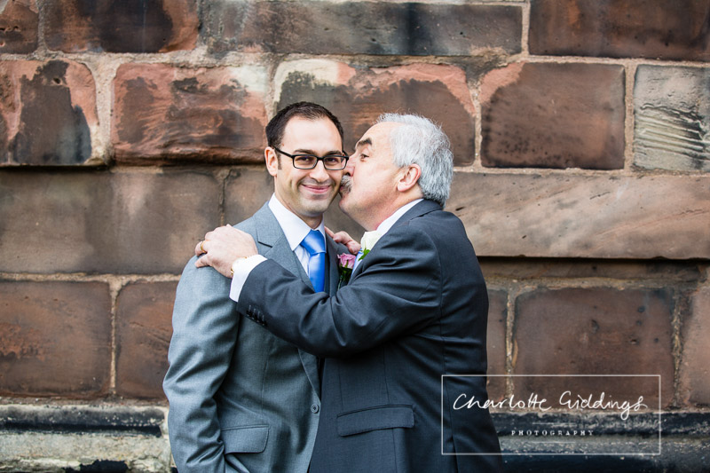 uncle joking around and kissing the side of grooms face finding it funny outside st. alkunds church