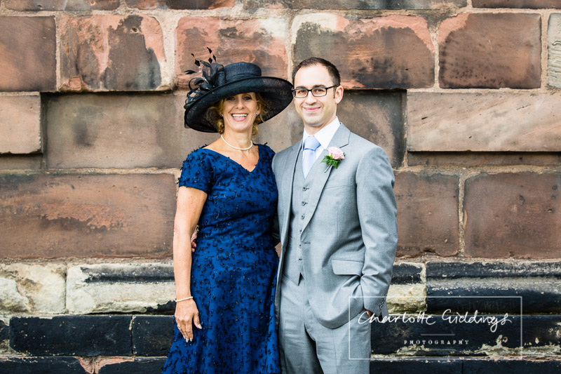 outside of st.alkmunds church whitchurch, groom with mother of the groom looking delighted for the ceremony