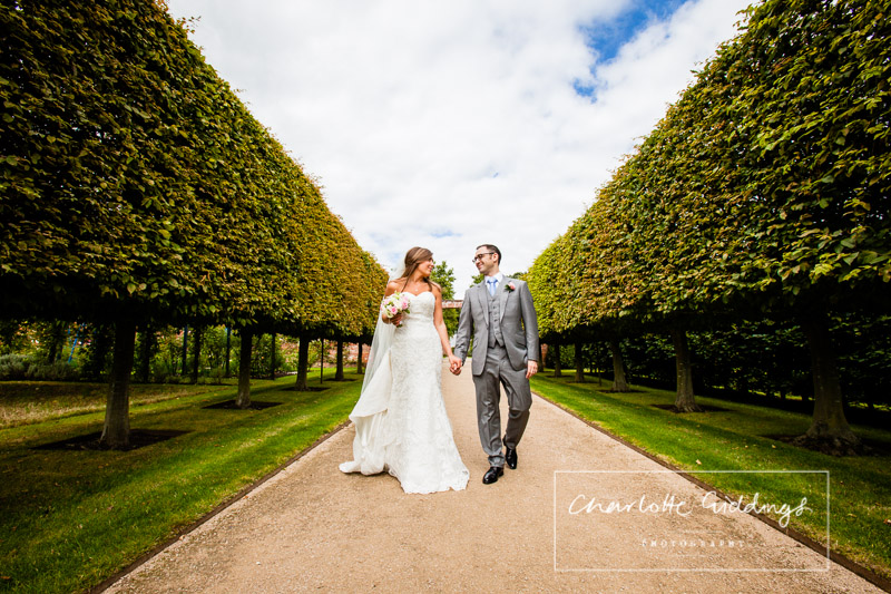 bride and groom walking hand in hand along tree lined path at summer wedding combermere abbey