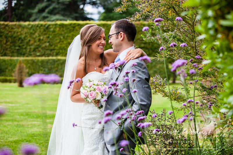summer wedding combermere abbey - bride and groom having a moment in the verbinia purple flowers giggling between themselves