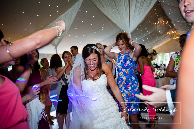 bride dancing with girlfirends in the pavillion at summer wedding combermere abbey