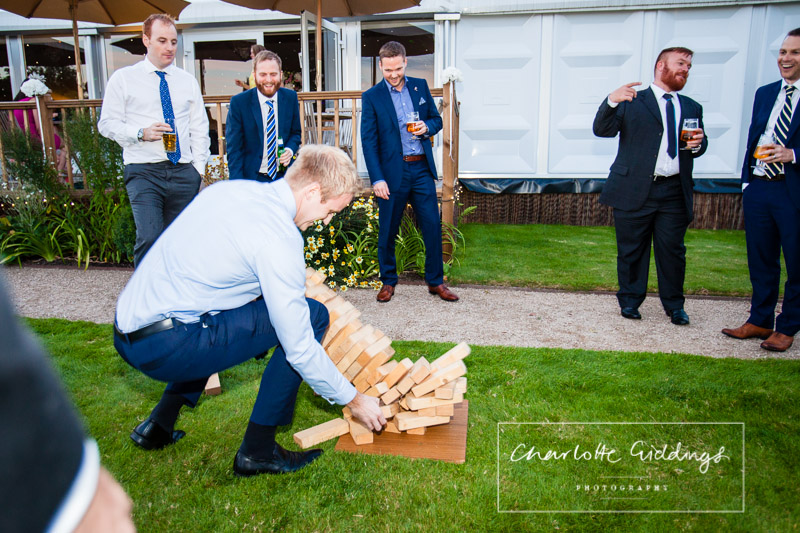 man trying to catch jenga as it comes crashing down at combermere abbey, whitchurch shropshire