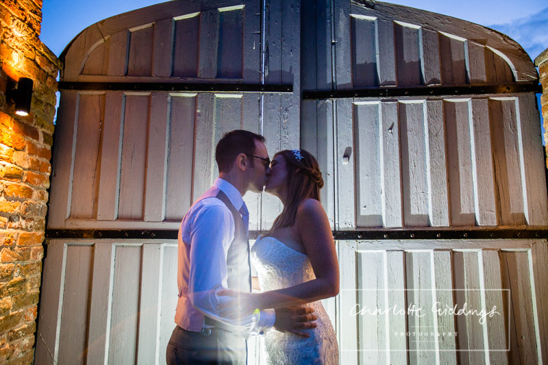 bride and groom kissing in front of the big gates at combermere abbey shropshire venue