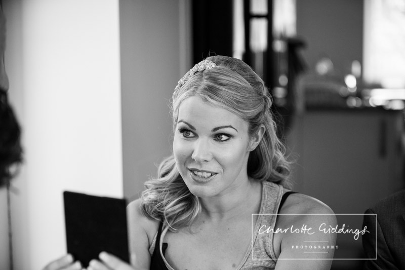 bride looking at hair and makeup in the mirror
