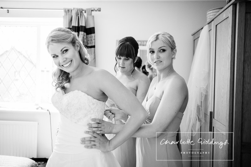 bride getting in her dress with bridesmaids help