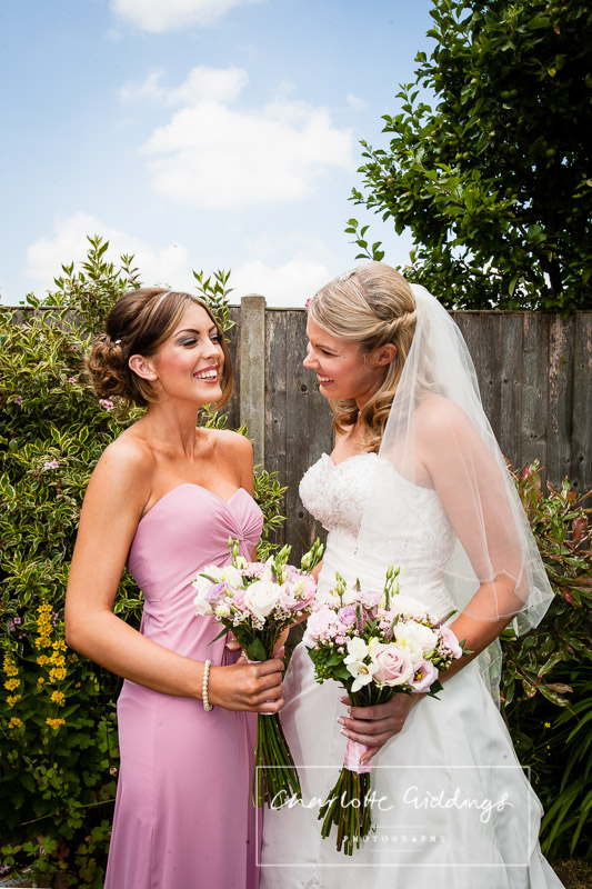 bride and bridesmaid giggling outside