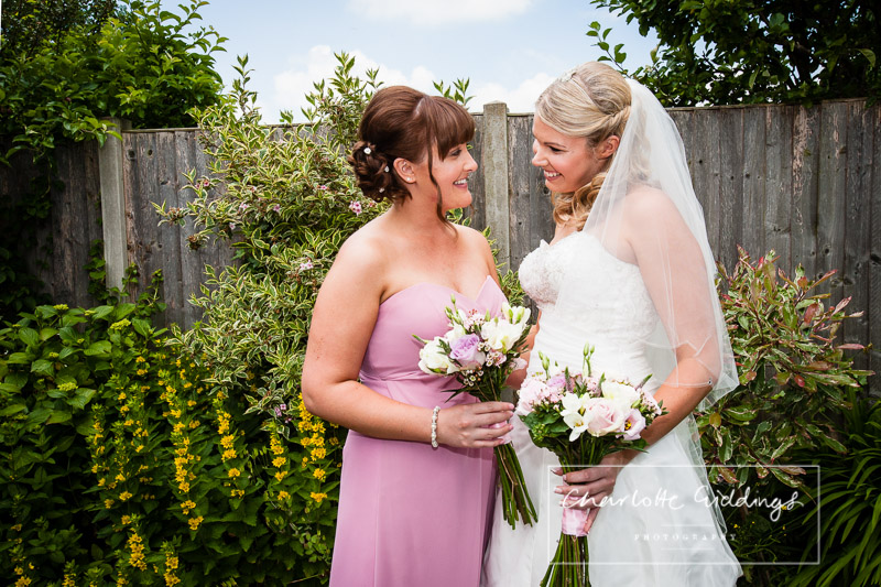 bride with made of honour looking at each other