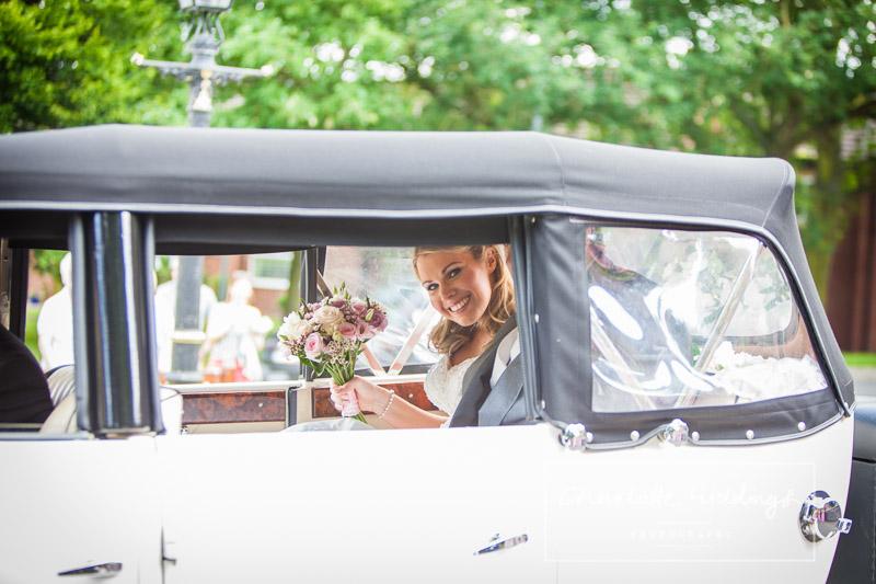 bride looking through the wedding car wind ow