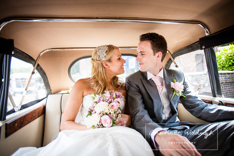 bride and groom in the wedding car looking adoringly at one another