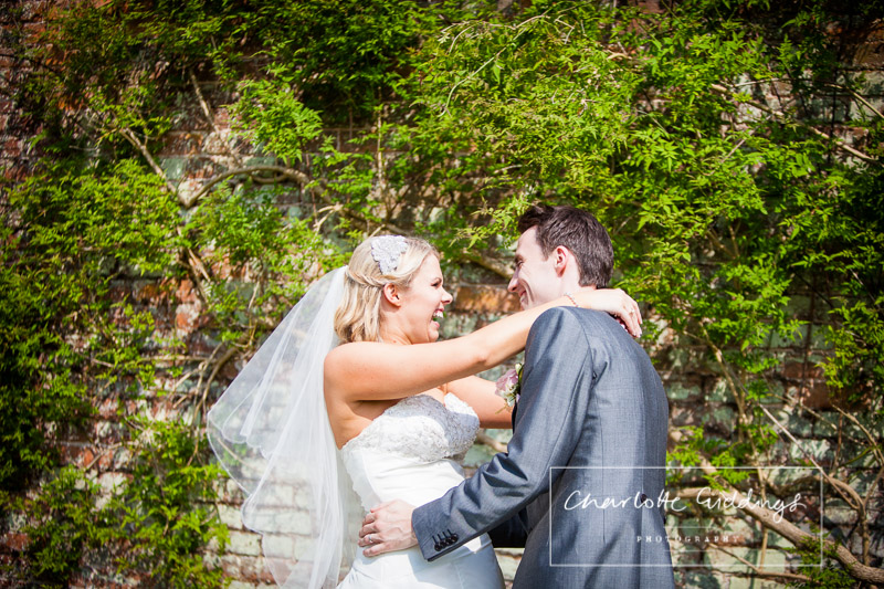 bride and groom laughing in combermere abbey grounds
