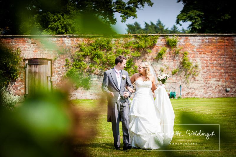 bride and groom walking through walled gardens