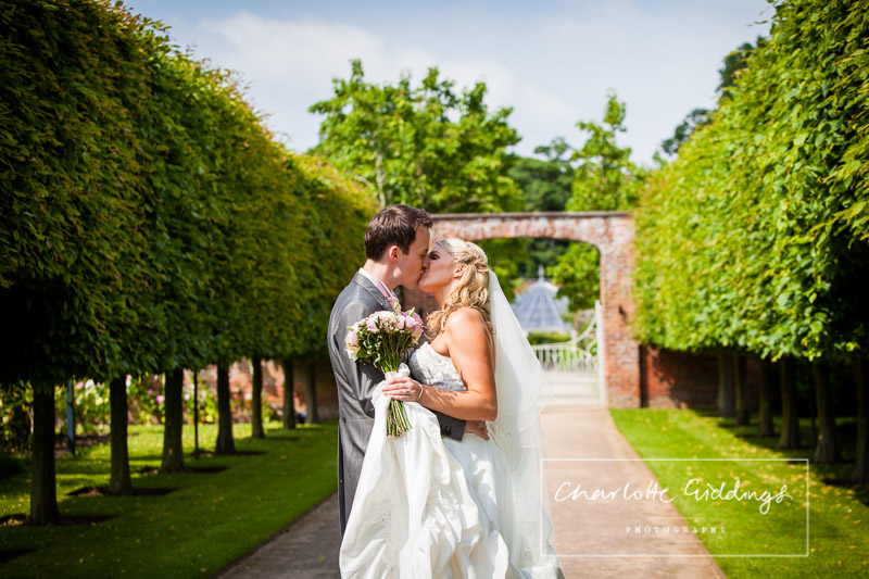bride and groom kissing in combermere abbey grounds