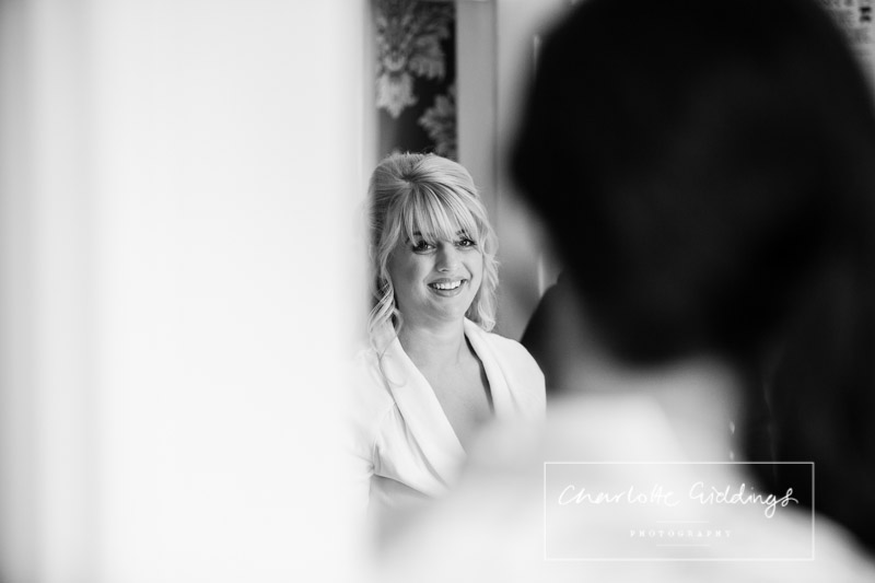 black and white photo of the bride getting ready in the morning looking happy