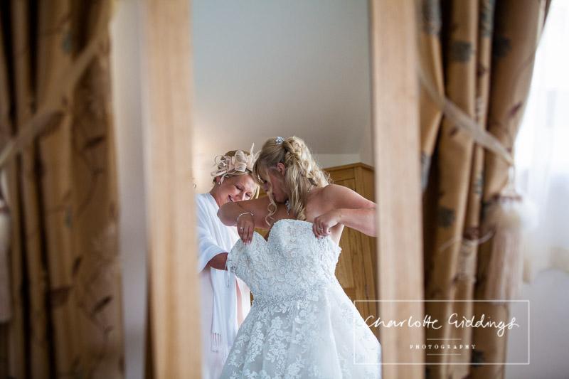 bride getting into her dress at heaton house farm wedding venue