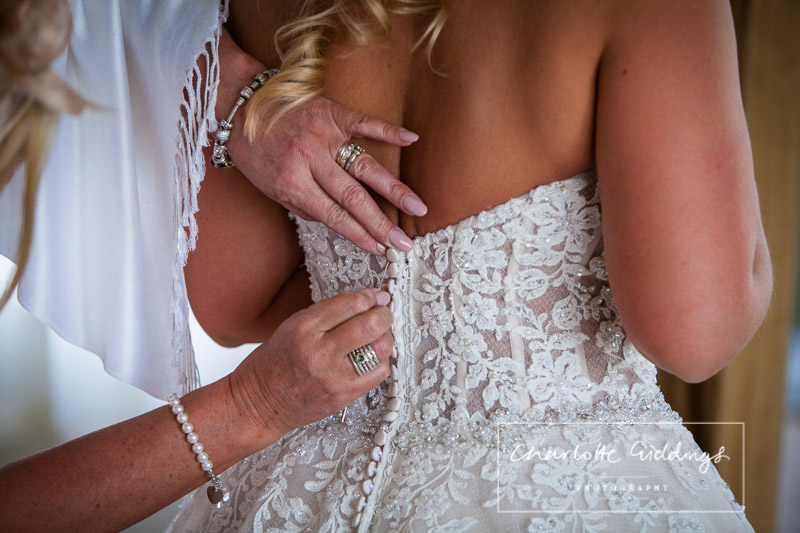 mother of the bride doing the finishing touches on brides wedding dress