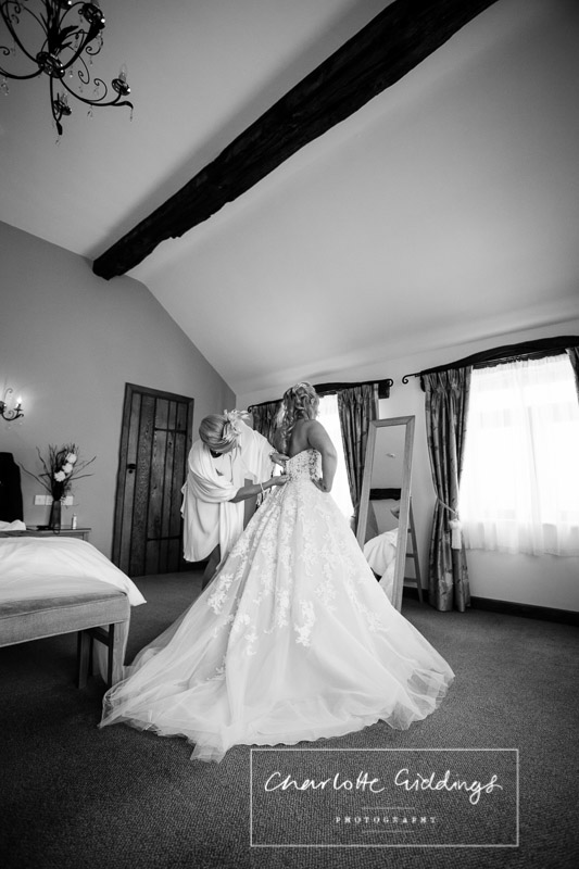 black and white shot of the bride getting in her wedding dress -charlotte giddings photography
