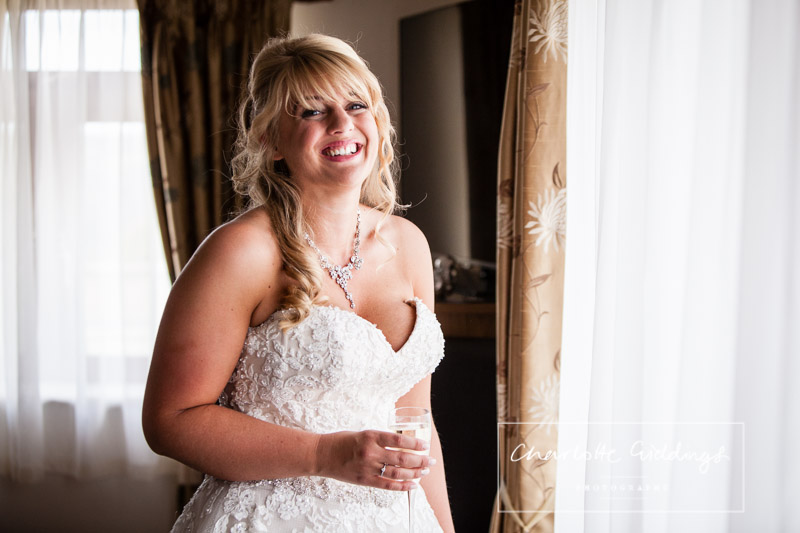 very excited bride with a glass of champagne in natural light - charlotte giddings photography