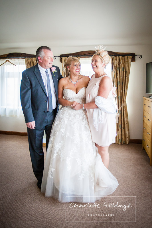 family portrait with bride, mother of the bride and father of the bride all laughing