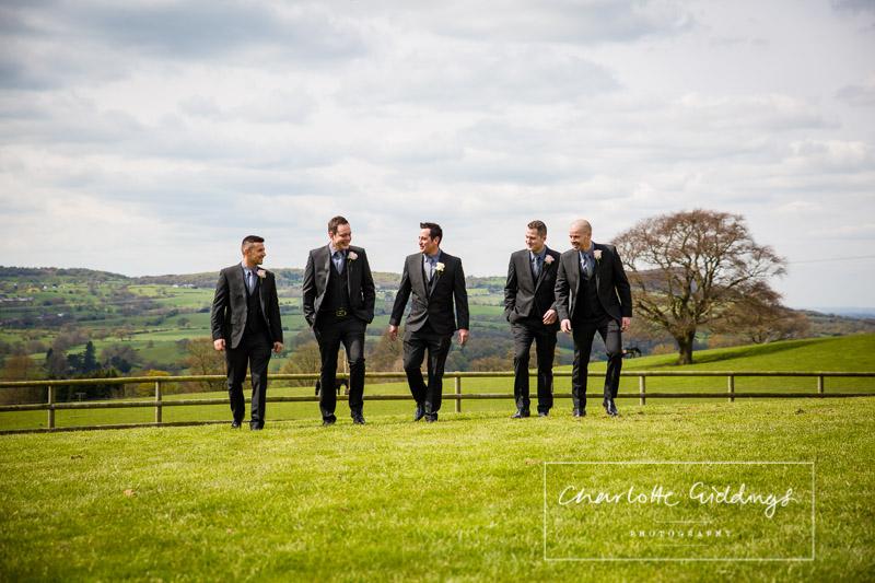 the groom and his groomsmen walking across grass at heaton house farm