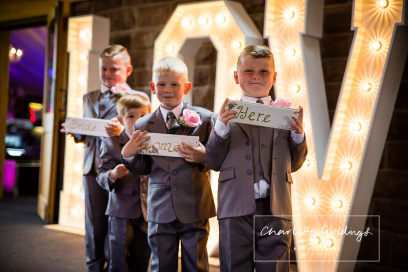 page boys with signs at heaton house farm wedding