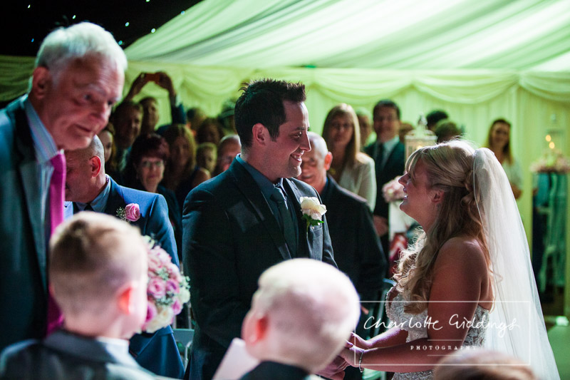 bride and groom looking at once another while doing their vowels