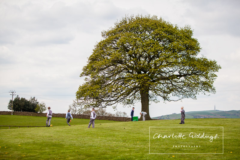young boys playing football around the sycamore tree at heaton house farm wedding venue