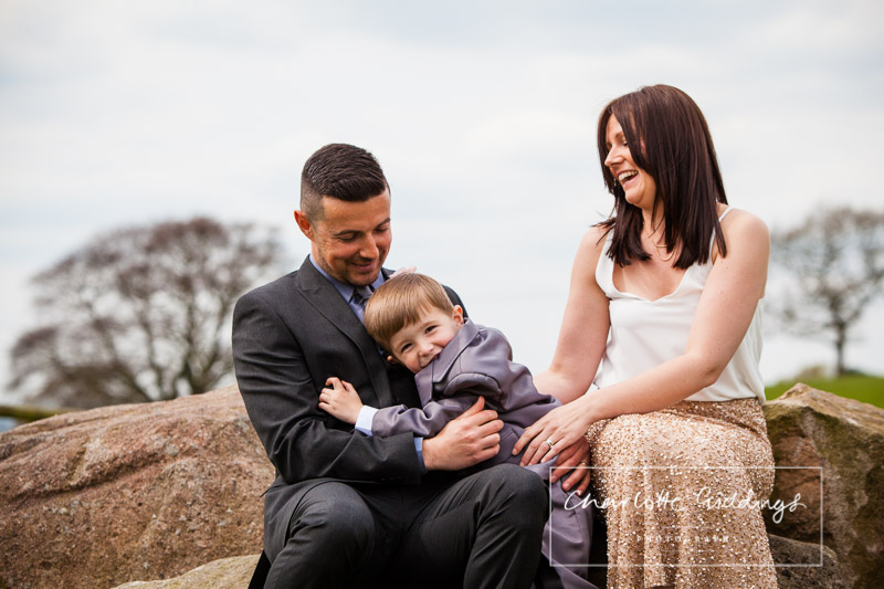 candid family photo with mum, dad and son at heaton house farm wedding venue