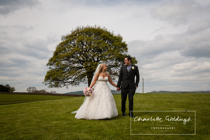 bride and groom walking across the grass looking at one another lovingly at heaton house farm