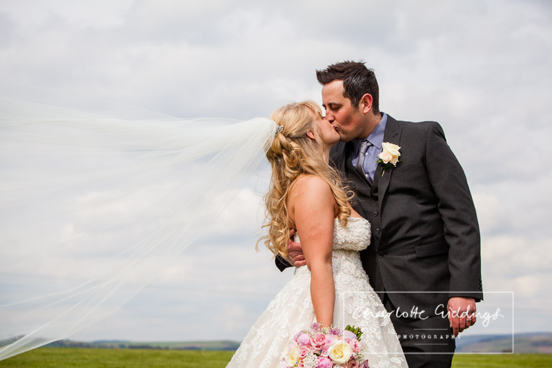 bride and groom having a kiss with the wind catching the brides veil - charlotte giddings photography