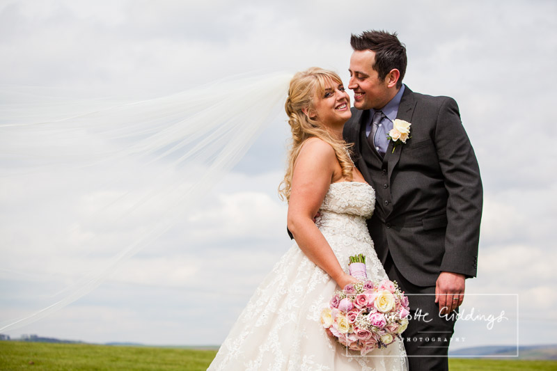 groom looking at his bride and bride looking at the camera holding her beautiful bouquet - charlotte giddings photography