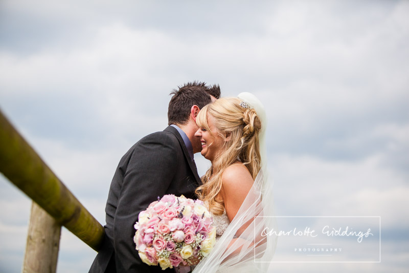 groom whispering in brides ear and laughing - charlotte giddings photography
