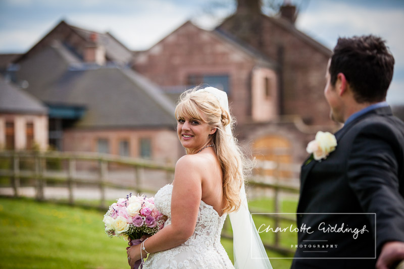 bride looking back at the camera with heaton house farm in the background